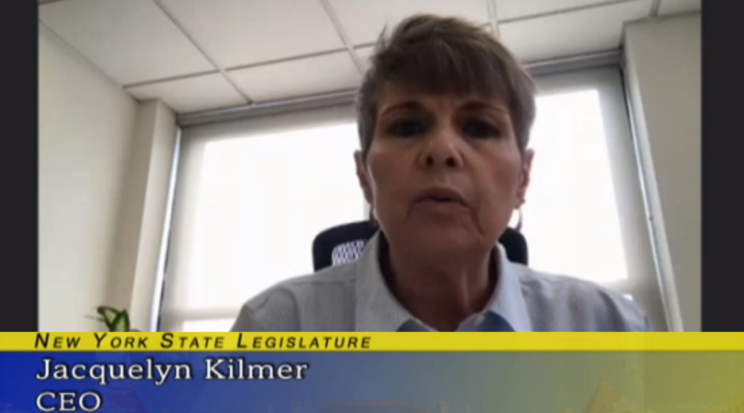 """Jacqui Kilmer speaking to the camera. A blue and gold graphic under her face says """"New York State Legislature; Jacqui Kilmer; CEO; Harlem United"""""""