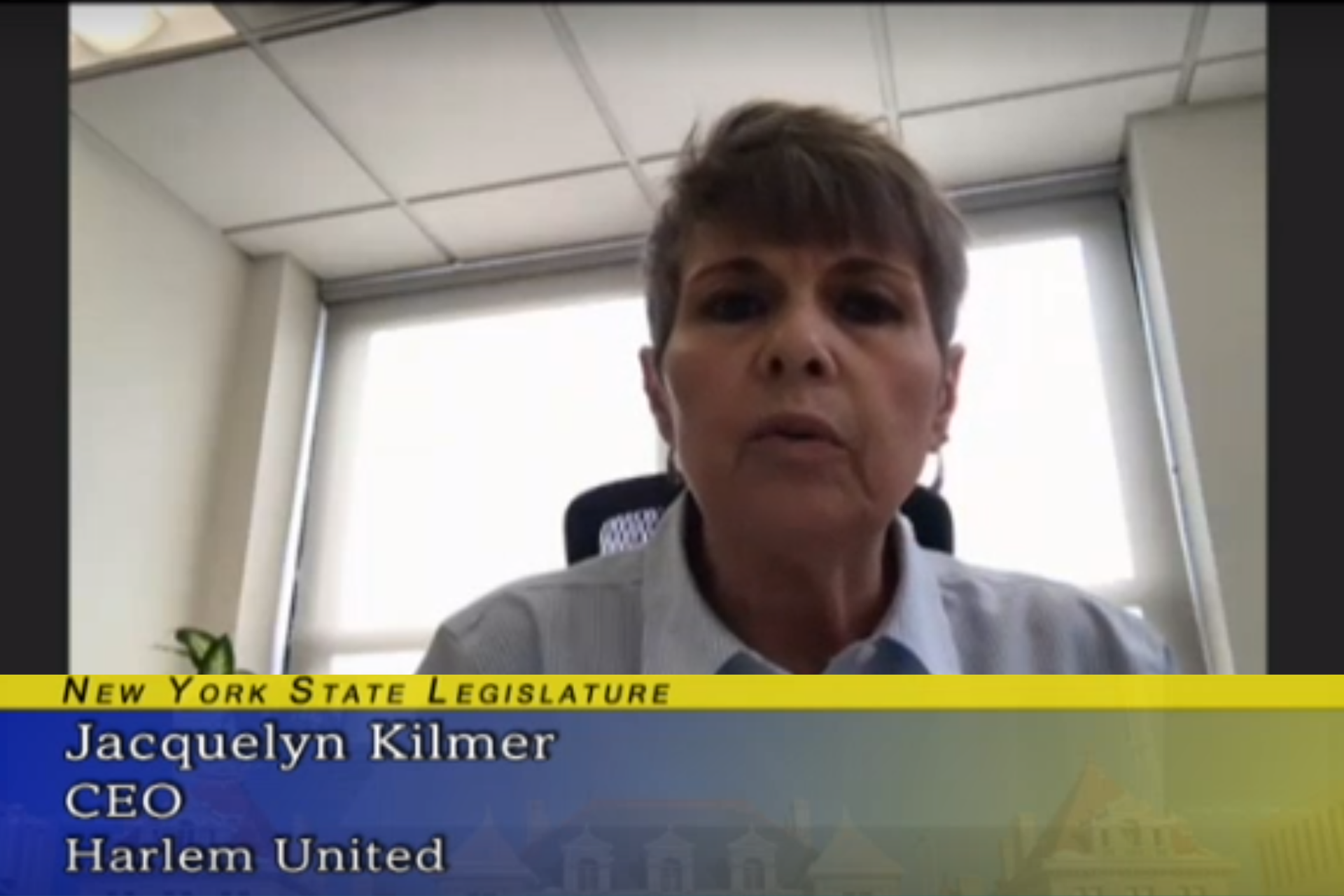 "Jacqui Kilmer speaking to the camera. A blue and gold graphic under her face says ""New York State Legislature; Jacqui Kilmer; CEO; Harlem United"""
