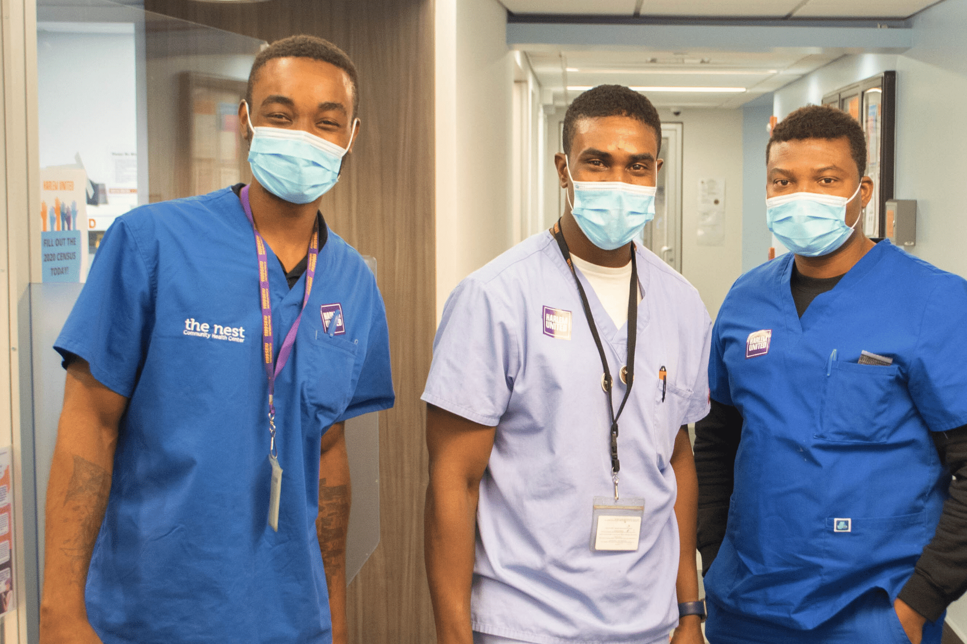Healthcare workers posing in clinic, wearing masks