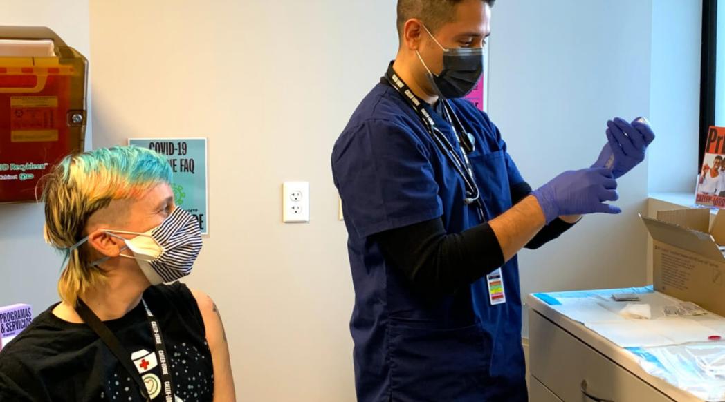 Healthcare worker prepares vaccine shot for waiting patient