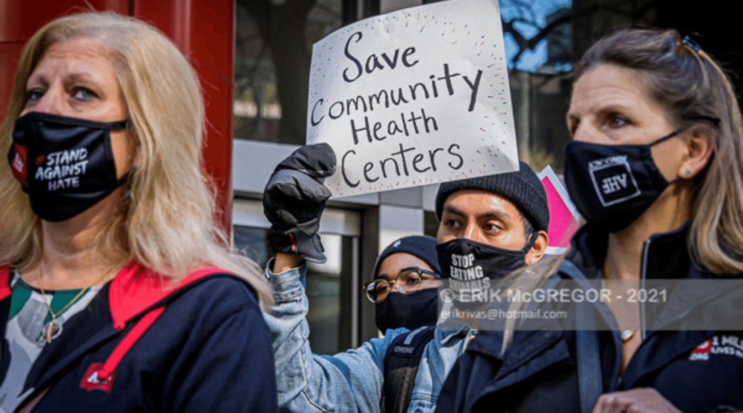 """Activists at a rally. Sign reads """"Save Community Health Centers"""""""