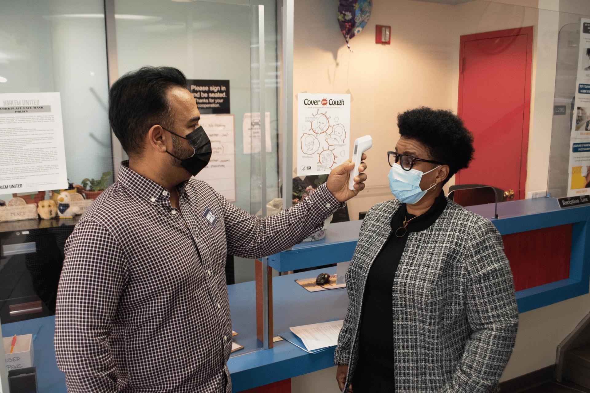 Staff take temperature at Harlem United facility